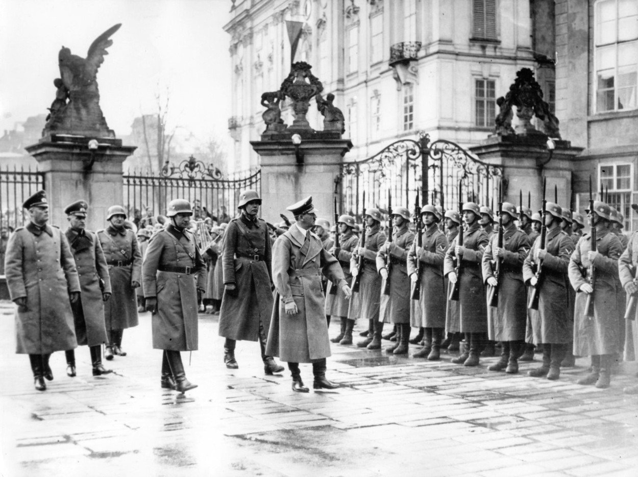 "The image from the Nazi Propaganda! shows Adolf Hitler marching past an honorary company in the Castle District in Prague, Czech Republic, after the invasion of the so-called ""Remainder of Czechia"" by the German Wehrmacht , on 16 March 1939. From here, he"